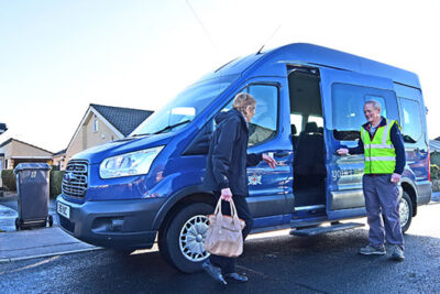 A passenger getting into the minibus