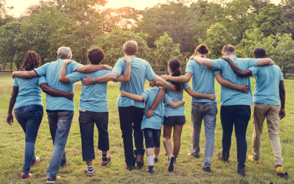 A group of people walking in a line with their arms around each other